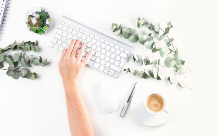 picture of a hand typing on a keyboard with a cup of coffee on the side