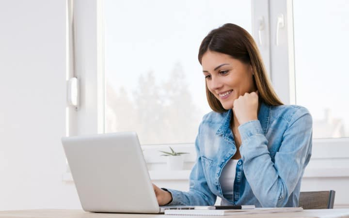 Woman typing on a laptop working from home as a virtual assistant