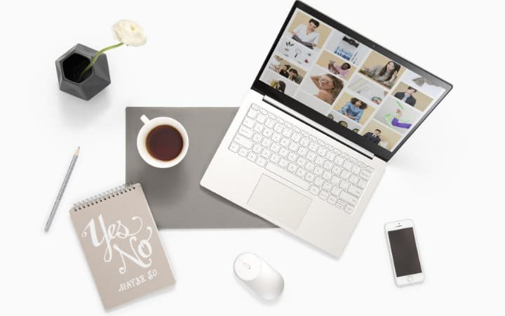 desk with a laptop, coffee, pen, notebook and flower vase