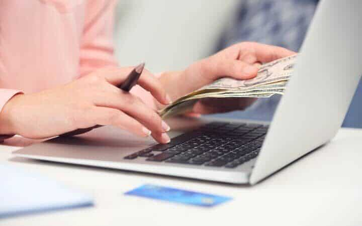 Woman typing on a laptop and making money