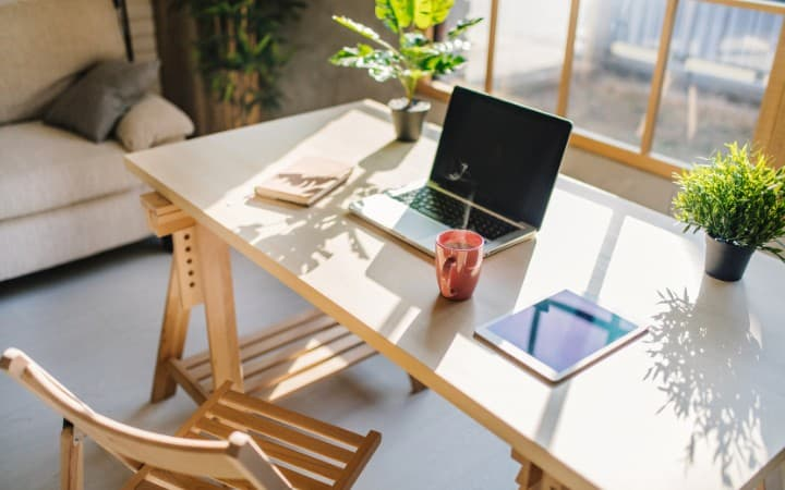 Minimalist home office desk with a laptop and tablet